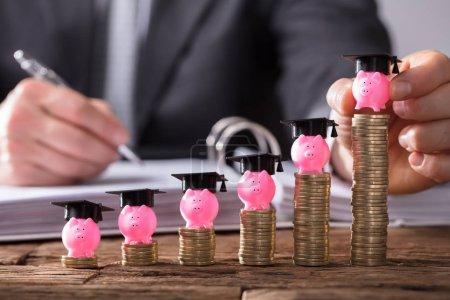 Photo pour La main de l'homme d'affaires plaçant la tirelire avec le plafond de graduation sur l'augmentation des pièces empilées sur le bureau en bois - image libre de droit