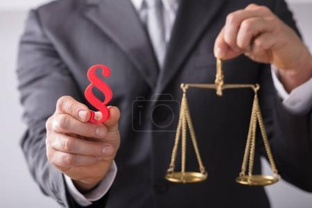 Close-up Of A Judge's Hand Holding Red Paragraph Symbol And Justice Scale