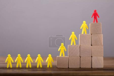 Red Figure Leading Yellow Human Figures On Top Of Wooden Blocks