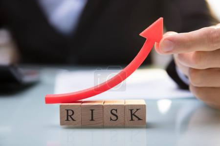 Close-up Of A Businessperson's Hand Holding Red Arrow Over Risk Blocks