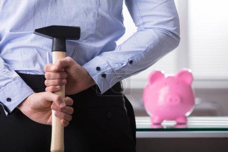 Businessperson Hiding Hammer In Front Of Piggy Bank