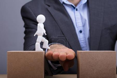 Close-up Of A Person's Hand Helping Human Figure While Walking Between Two Cardboard Box