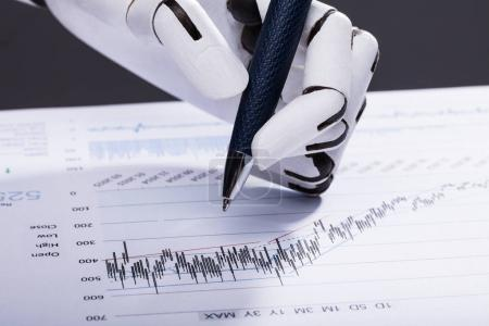 Elevated View Of A Robotic Hand Holding Pen Over Financial Document