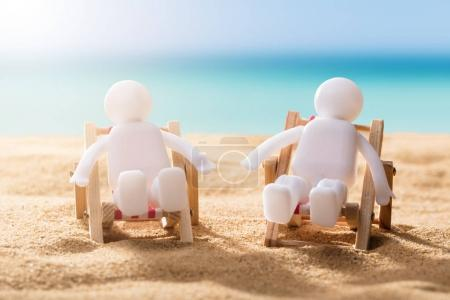 Close-up Of Two Human Figures Relaxing On Deck Chairs At The Beach