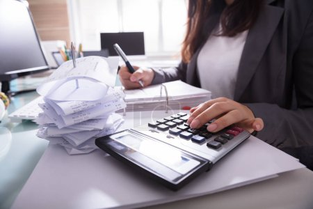 Photo pour Gros plan de la main d'une femme d'affaires calcul facture avec calculatrice - image libre de droit