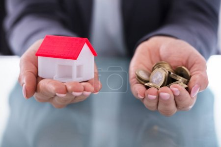 Close-up Of A Businessperson's Hand Holding Coins And House Model
