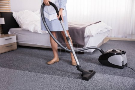 Low Section View Of A Janitor Using Vacuum Cleaner For Cleaning Carpet In Hotel Room