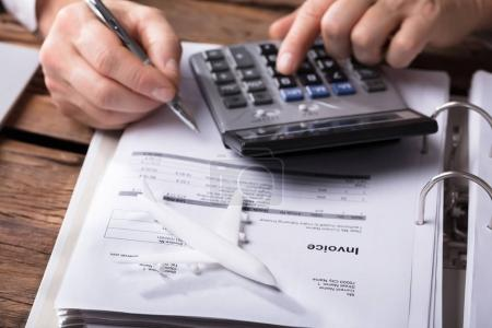 Close-up Of A White Aeroplane In Front Of Businessperson Calculating Invoice