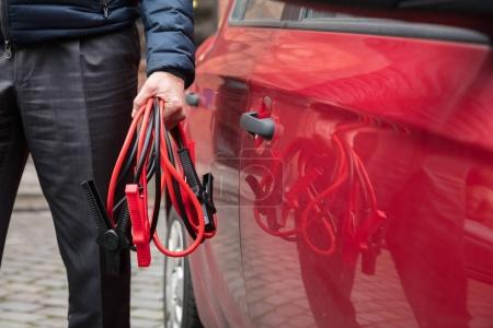 Photo pour Gros plan de la main d'une personne tenant des câbles de pullover près de la voiture rouge - image libre de droit