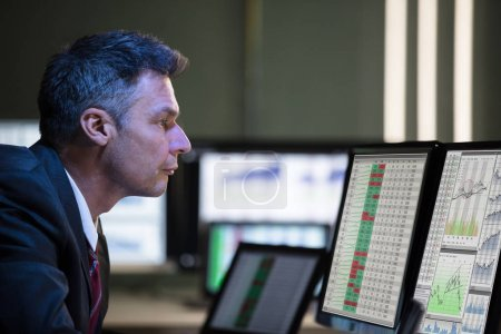 Side View Of A Mature Male Stock Market Broker Analyzing Graph On Multiple Computer Screen