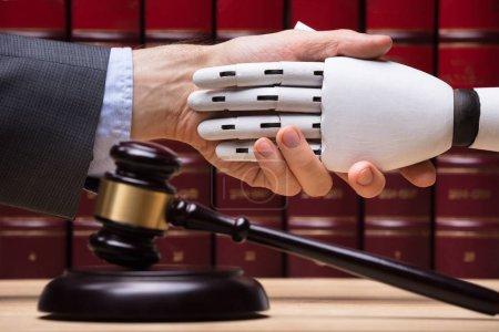 Photo pour Robot, serrant la main de juge près de marteau sur le bureau en bois - image libre de droit
