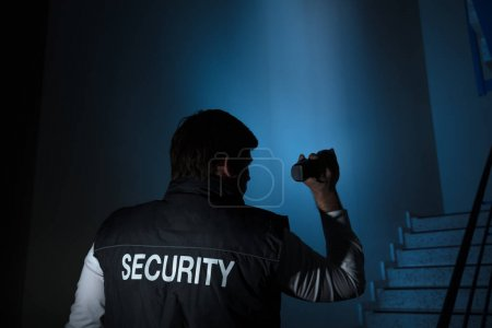 Rear View Of A Security Guard Standing Near Stairway Holding Flashlight