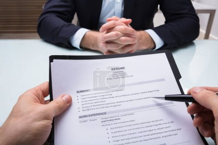 Businessperson's Hand Holding Resume While Interviewing Applicant