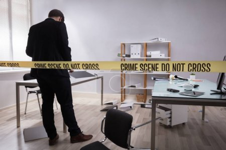 Investigator Collecting Evidence In Office Behind Yellow Crime Scene Tape