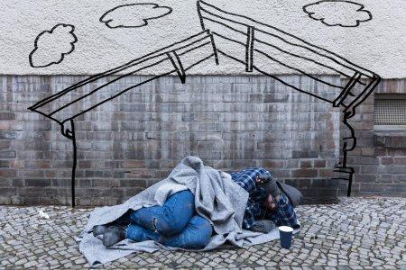 Mendiant sans abri dormant sur la rue sous le croquis d'une maison