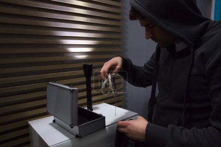 Close-up Of A Thief In Hoodie Stealing Jewelry