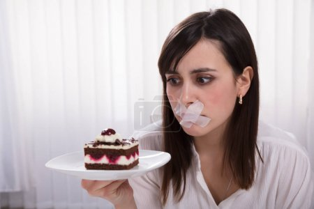 Young Woman With Sticky Tape Over Her Mouth Holding Slice Of Cake On Plate