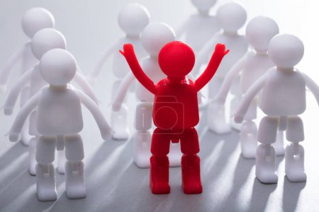 Close-up Of A Red Human Figure With Arm Raised Standing With Team In A Row