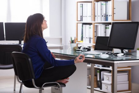 Photo for Young Businesswoman Sitting On Chair Meditating In Office - Royalty Free Image