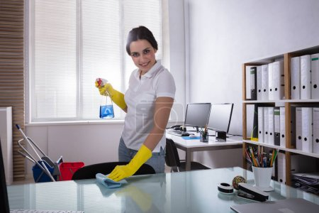 Portrait Of A Happy Female Janitor Wearing Yellow Gloves Cleaning Desk With Rag