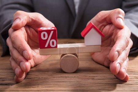 Photo pour Homme d'affaires protégeant l'équilibre entre maisons et pourcentage sur bureau en bois - image libre de droit