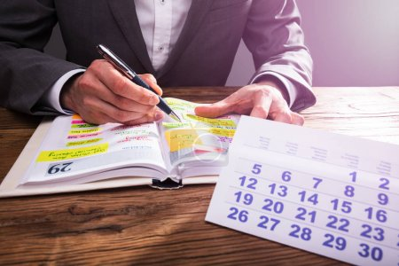 Businessperson's Hand Checking Schedule In Diary With Calendar On Wooden Desk