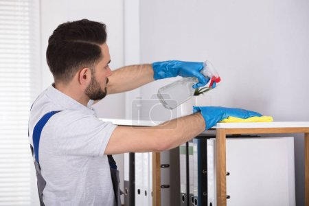 Close-up Of A Young Male Cleaner Cleaning Shelf At Workplace