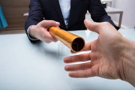 Photo pour Gros plan de la main de l'homme d'affaires en passant la baguette d'or à son partenaire au bureau - image libre de droit