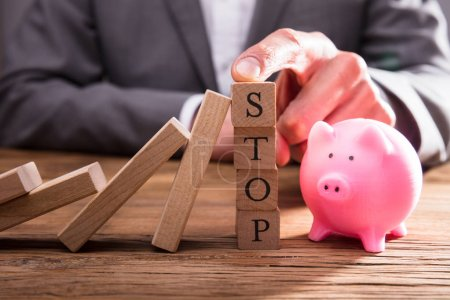 Person's Finger On Stop Wooden Blocks Stopping Dominos From Falling Over Piggybank