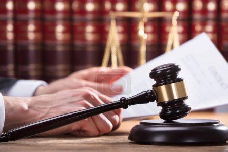Photo pour Gros plan d'un marteau devant une main humaine tenant un document en salle d'audience - image libre de droit