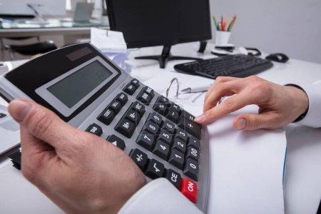 Photo pour Gros plan de la main d'un homme d'affaires à l'aide d'une calculatrice au bureau - image libre de droit