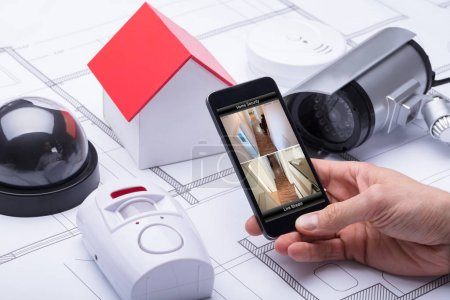 Architect Using Home Security System On Mobile Phone Near Security Equipments And House Model