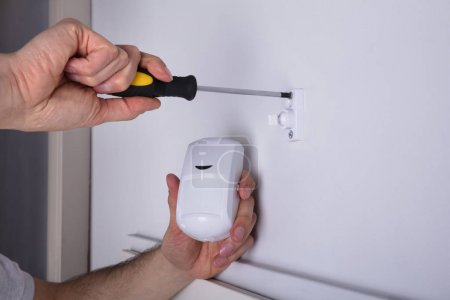 Close-up Of A Young Male Electrician Installing Security System Door Sensor On Wall