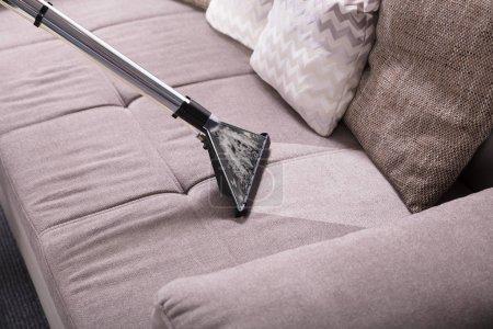 Foto de Vista de ángulo alto de aspiradora en sucio sofá en casa - Imagen libre de derechos