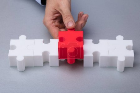 A Person's Hand Placing Red Piece Between White Jigsaw Puzzle