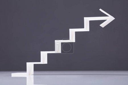 White Increasing Staircase Arrow On Grey Backdrop