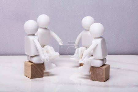 Four White Human Figurines Sitting On Wooden Block Having Meeting Together