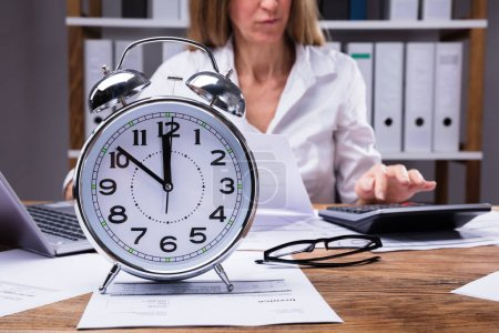 Close-up Of An Alarm Clock On Invoice In Front Of Businesswoman Working In Office