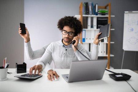 Photo pour Souriant jeune entrepreneur travail multitâche sur lieu de travail - image libre de droit