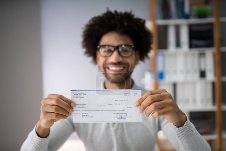 Photo pour Midsection Of Smiling Businessman Holding Cheque In Office - image libre de droit