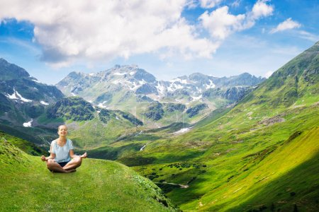 Photo for Happy Young Woman Sitting On Green Mountain Doing Meditation Against Cloudy Sky - Royalty Free Image