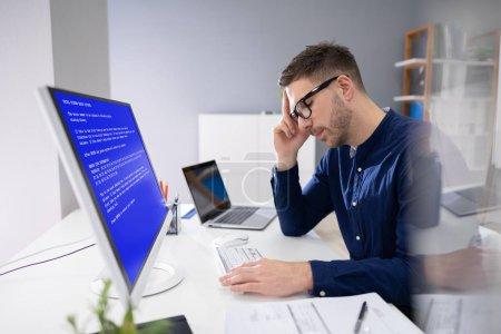Photo pour Homme inquiété à l'ordinateur avec l'écran de défaillance de système au lieu de travail - image libre de droit