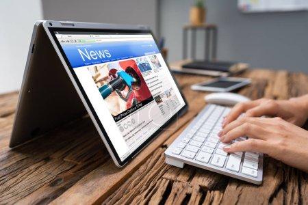 Photo pour Cropped Image Of Businesswoman lecture Nouvelles sur ordinateur portable au bureau - image libre de droit