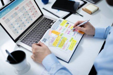 Photo pour Gros plan de l'homme d'affaires Horaire de rédaction au calendrier Journal au bureau - image libre de droit