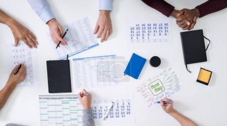 Photo pour Groupe de personnes Projet de planification à l'aide de graphiques et de calendriers de Gantt - image libre de droit