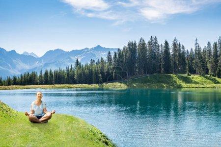 Joven alegre sentada cerca de la orilla del lago haciendo yoga contra el cielo nublado