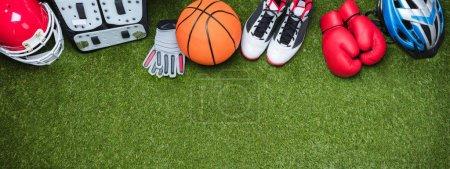 Photo pour Vue Panoramique De Divers Accessoires De Sport Sur Le Faux Fond Vert D'herbe De Gazon - image libre de droit