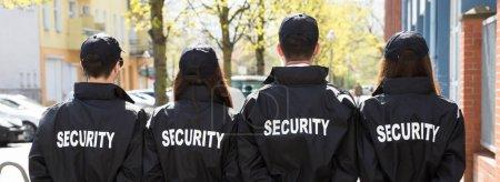 Photo pour Gardes de sécurité avec les mains derrière le dos debout dans une rangée à l'extérieur - image libre de droit