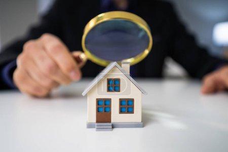 Photo pour Gros plan d'un modèle de maison vu à travers le verre grossissant sur la table - image libre de droit