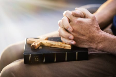 Photo for Sunlight Falling On Hand Over Bible While Praying - Royalty Free Image